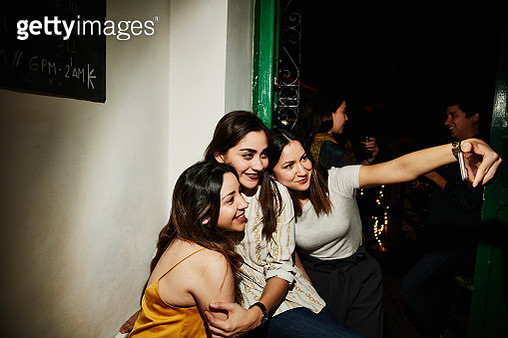 Smiling female friends taking selfie with smart phone while hanging out in night club - gettyimageskorea