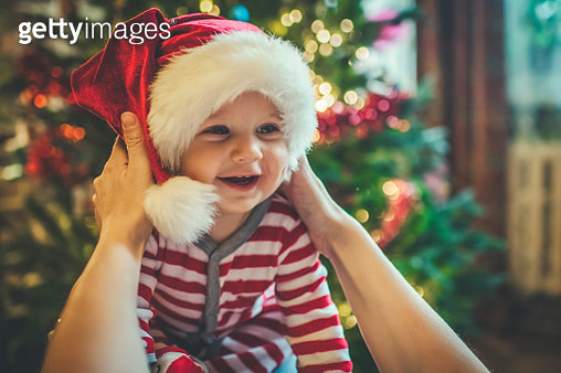 Cute boy with mother near Christmas tree indoors - gettyimageskorea