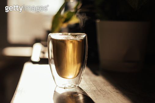 Putting tea bag into glass cup full of hot water - gettyimageskorea