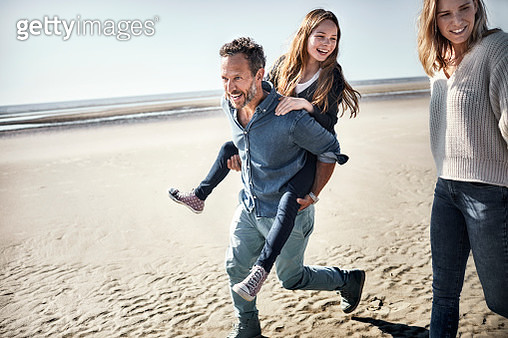 Father carrying daughter piggyback on the beach - gettyimageskorea