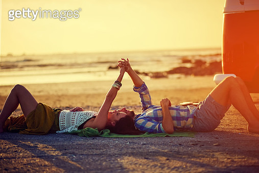 Shot of an affectionate young couple holding hands while lying on the beach - gettyimageskorea