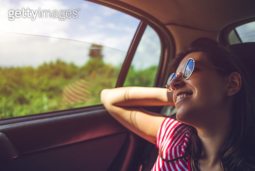 Young woman on the back seat of a car, enjoying ride - gettyimageskorea