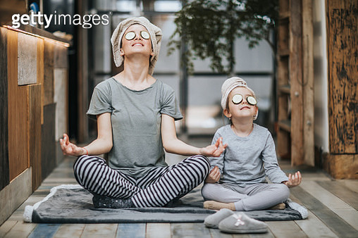 Mother and little girl taking care of their bodies in the morning while doing Yoga meditation exercises at home. Their hair is wrapped in towels while cucumber is on her eyes. - gettyimageskorea