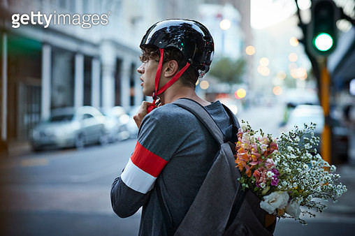 Bike messenger carrying flowers in backpack - gettyimageskorea