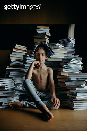Boy Sitting Against Stack Of Books - gettyimageskorea