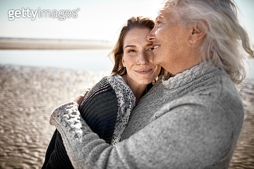 Affectionate senior woman with her adult daughter on the beach - gettyimageskorea