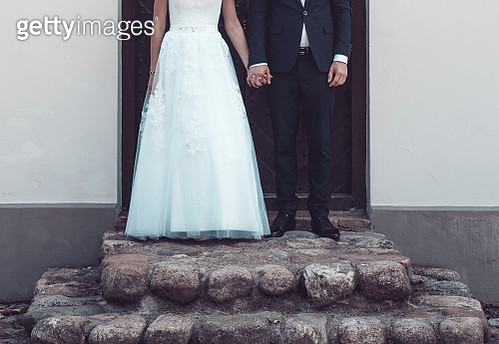 Low Section Of Bride And Bridegroom Holding Hands While Standing On Steps - gettyimageskorea