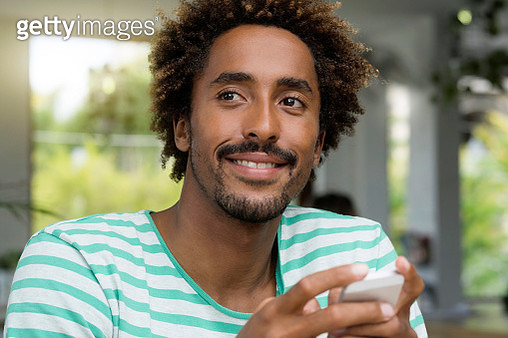 Smiling man with smartphone in a cafe - gettyimageskorea