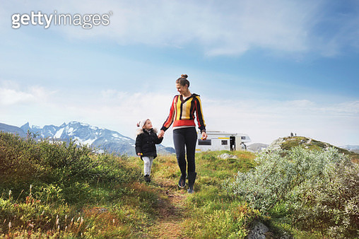 Mother with daughter walking on wild road, campervan and mountains in background - gettyimageskorea