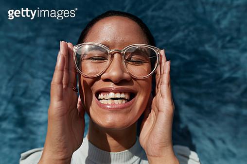 Smiling woman wearing eyeglasses against blue wall - gettyimageskorea
