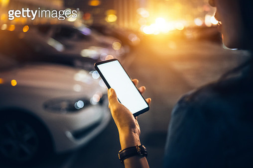 Woman using smartphone while walking to her car in car park at night - gettyimageskorea