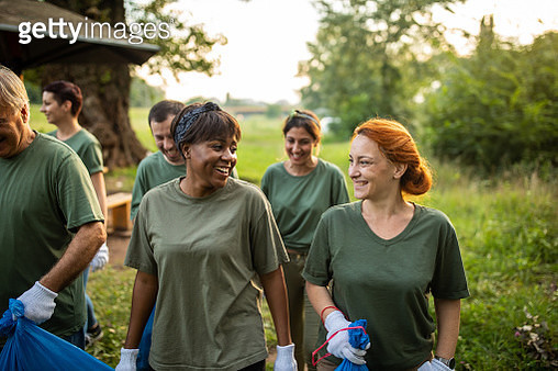 Happy volunteers bonding after environmental cleanup at public park - gettyimageskorea