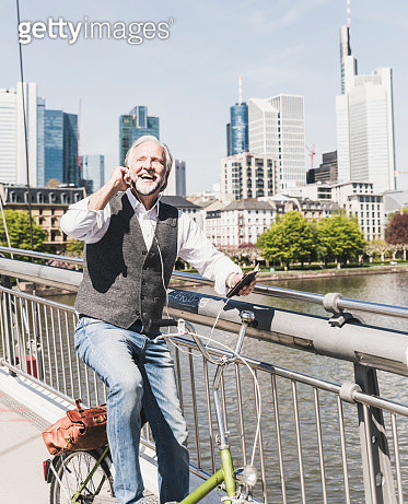 Happy mature man with earbuds, cell phone and bicycle on bridge in the city - gettyimageskorea