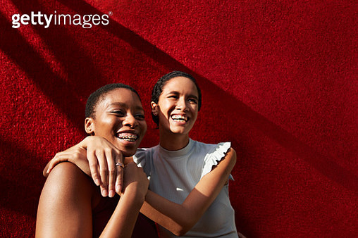 Smiling young woman standing with female friend against red wall - gettyimageskorea