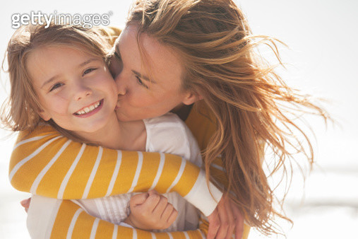 Close up of mother kissing daughter at beach - gettyimageskorea