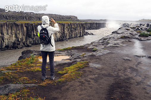 Selfoss is a waterfall on the river Jökulsá á Fjöllum in the north of Iceland. The river drops over a number of waterfalls over about 30 km before flowing into Öxarfjörður. Woman seen from behind in white anorak with hood and backpack, wet weather. - gettyimageskorea