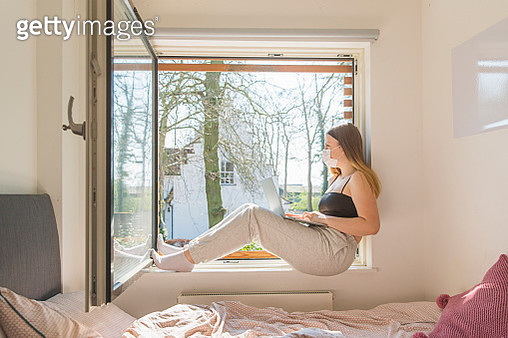 Teenage girl with mask looking out of window - gettyimageskorea