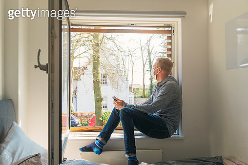 Man with mask looking out of window - gettyimageskorea