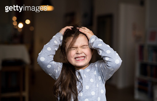 Front view portrait of small girl standing indoors at home, gritting teeth. - gettyimageskorea