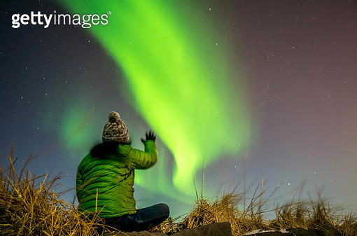 Woman reaching for the Northern Light in Reykjavik, Iceland - gettyimageskorea
