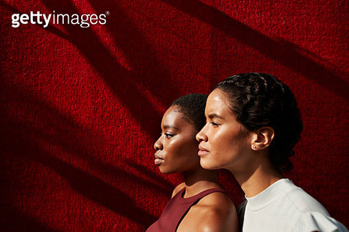 Side view of women standing against red wall - gettyimageskorea