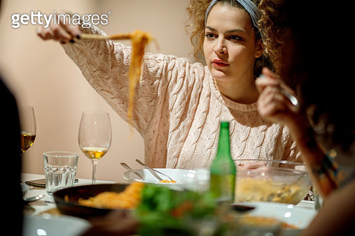 Young woman take spaghetti while dining with roommates italian food at home - gettyimageskorea