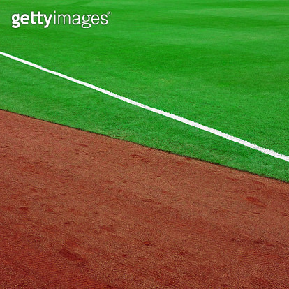 Close up of sports field with green grass and red dirt and white stripe. - gettyimageskorea
