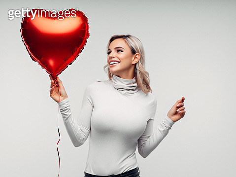 Beautiful young woman with heart shape air balloon - gettyimageskorea