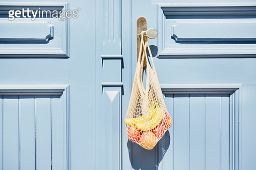 Reusable shopping bag with apples and bananas hanging at blue wooden door - gettyimageskorea