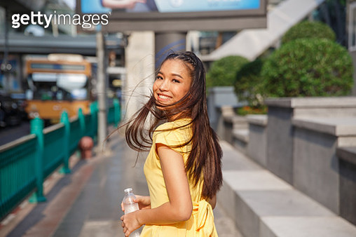 A beautiful Asian girl in a yellow dress with a smile turned around on the street of Bangkok. Her hair flutters in the wind. In her hand she holds a plastic bottle. - gettyimageskorea