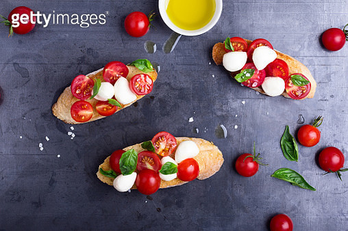 Caprese bruschetta with flavorful cherry tomatoes, fresh basil, and mozzarella on toasted bread, traditional Italian summer  appetizer, everyday messy situation at home kitchen viewed from above - gettyimageskorea