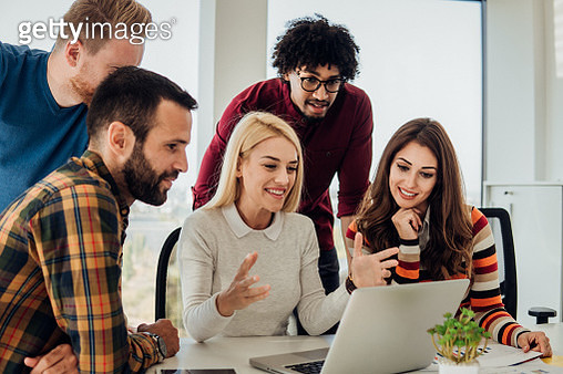 Business woman looking at laptop with coworkers - gettyimageskorea