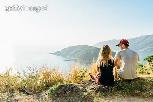 Young couple relax, on hillside above sea - gettyimageskorea