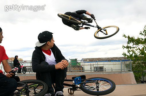 Teenagers watching a friend jumping on a BMX Bike - gettyimageskorea