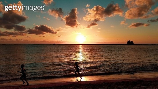 Silhouette Siblings Running At Beach Against Sky During Sunset - gettyimageskorea