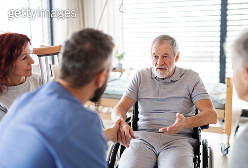 A doctor or healthcare worker talking to senior patients. - gettyimageskorea