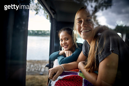 Portrait of two happy young women lying on a blanket in an off-road vehicle - gettyimageskorea