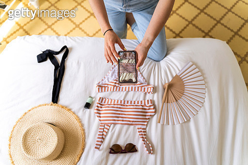 Woman taking smartphone picture of bikini on bed - gettyimageskorea