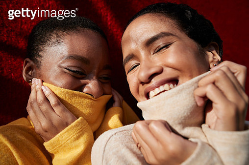 Smiling young female friends wearing turtleneck sweaters against red wall - gettyimageskorea