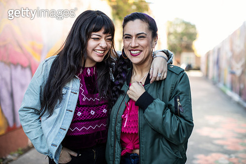 Two Latina Friends Laughing While Standing in Mural Alley in San Francisco's Mission District - gettyimageskorea