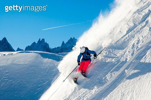 Skier skiing through fresh powder down steep mountainside, Chamonix, France - gettyimageskorea