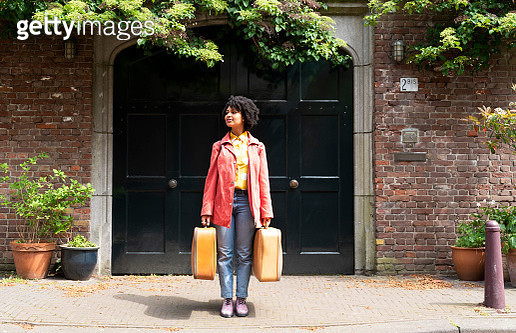A young woman with suitcases in the city. - gettyimageskorea