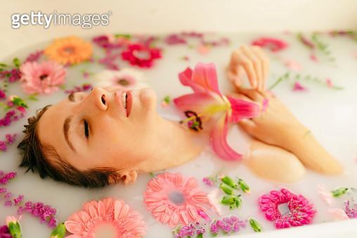 Young woman amidst flowers taking milkbath in bathtub at spa - gettyimageskorea