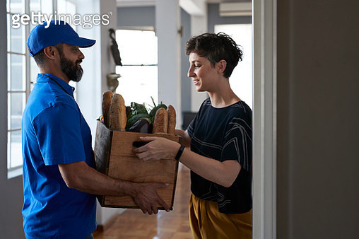 Courier delivering goods to woman in stylish apartment - gettyimageskorea