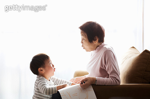 Senior woman and boy playing at home together - gettyimageskorea