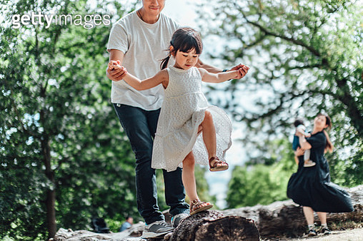 Caring young Asian father holding hands of his little daughter and assisting her to walk along a tree trunk outdoor on a sunny day - gettyimageskorea