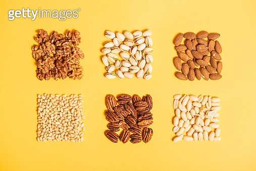 Six varieties of different nuts on a plain yellow background, horizontal composition - gettyimageskorea