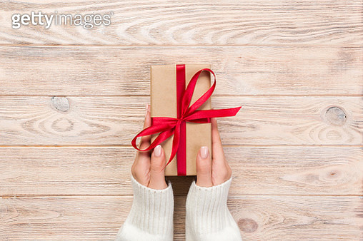 Cropped Hands Of Woman Holding Gift Box On Wooden Table - gettyimageskorea