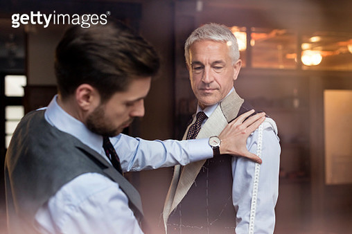 Tailor fitting businessman for suit in menswear shop - gettyimageskorea