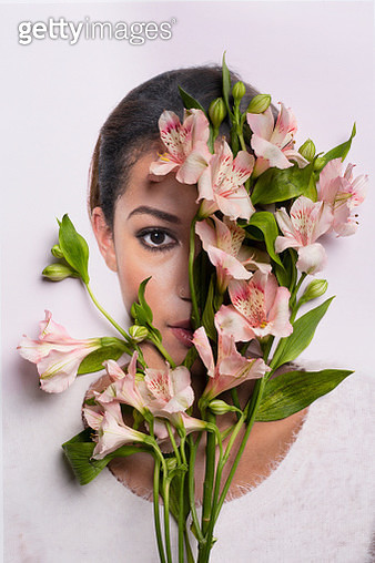 Young woman hiding behind flowers - gettyimageskorea